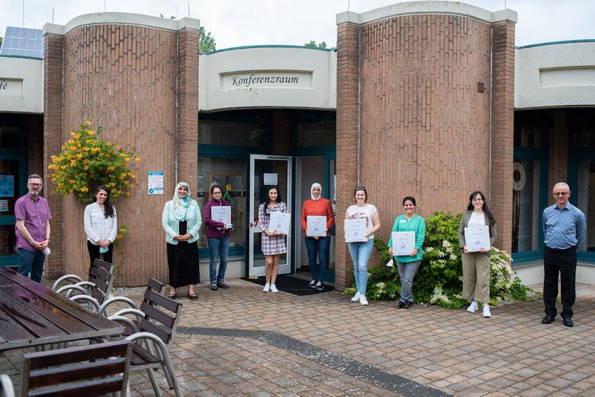10 Personen stehen vor einem Gebäude und halten Unterlagen in der Hand. Vor dem Gebäude steht die Aufschrift 'Konferenzraum'.