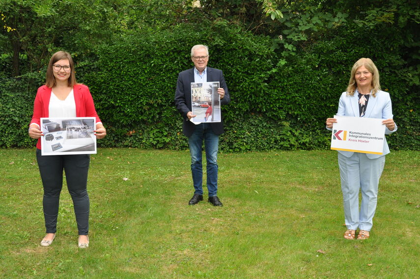 Alexandra Schodrowski, Klaus Schumacher und Filiz Elüstü stehen auf einer Wiese und halten Plakate in den Händen.
