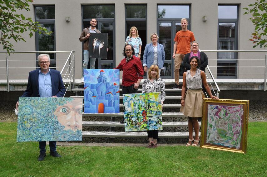 Künstler und Veranstalter halten Bilder in den Händen und werben für die Interkulturelle Kunstausstellung.
